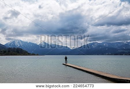 Young man standing alone on the jetty in the tegernsee lake and looking at the blue mountains in the famous tourist resort of the Bavarian Alps, Bavaria, Germany, Europe