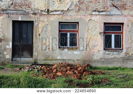 Abandoned old ruined house closeup of dilapidated front doors with missing door knob, two windows, partially fallen facade and red bricks in front on uncut grass