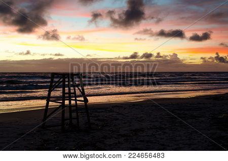 Lifeguard watchtower in silhouette in a sunrise in a beach with sun colors painting sky.