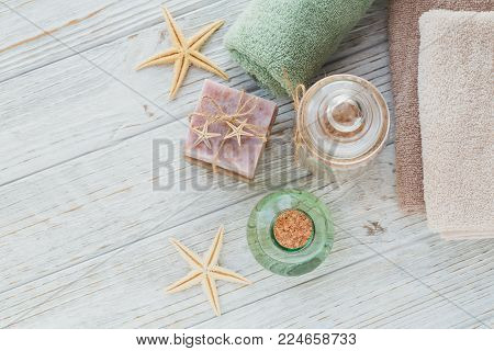 Spa products for facial and body care. Natural sea salt, homemade soap, massage oil and colorful towels. Spa and bodycare concept. poster