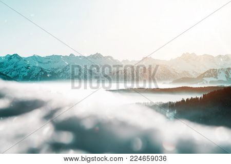 Distant snow-capped mountain ranges in a winter landscape lit by the warmth of the glow from the sun rising above steep valleys with low lying mist
