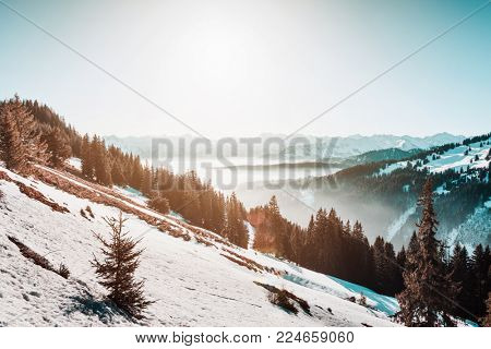 Snowy cold alpine landscape in winter with mist clinging to steep forested valleys and distant mountain ranges