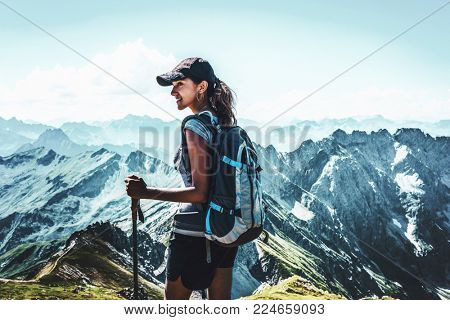 Attractive young woman trekking in the Allgau Alps on Grosser Daumen turning to watch something to the side with a smile against a backdrop of high rugged alpine mountains