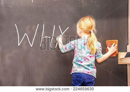 Cute little girl writing why on chalkboard in a classroom