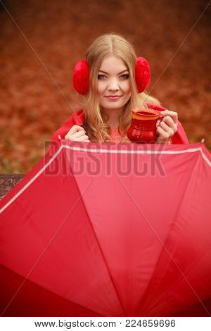 Happiness carefree and fall concept. Young woman relaxing in autumn park on bench under umbrella enjoying hot drink holding mug with warm beverage. Orange leaves background