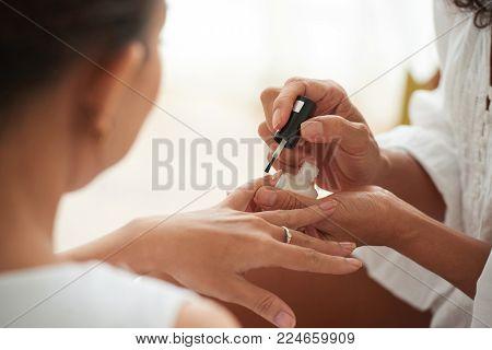 Close-up image of manicurinst applying nail polish