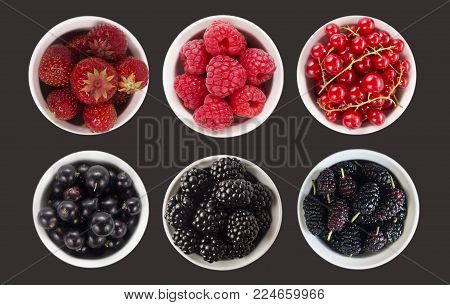 Blue and red fruits and berries isolated on black. Sweet and juicy berry with copy space for text. Top view. Mulberries, blackberries, currant, strawberry and raspberry. Collage of different fruits and berries. Berry on a black background.