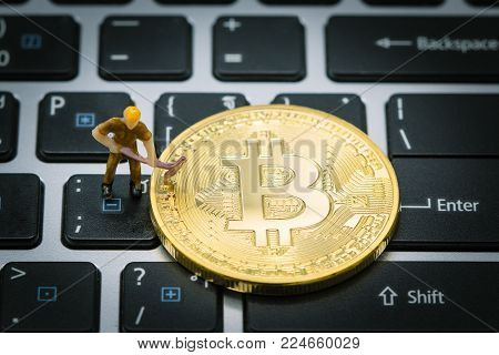 A little miner is digging for Golden bitcoin digital currency on keyboard or laptop. using as background business, Electronic money exchange concept, conceptual image of bitcoin mining and trading.