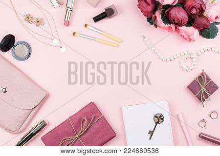 Beauty blog concept. Woman fashion accessories, flowers, cosmetics and jewelry on pink background, copyspace. Womens Day concept, top view