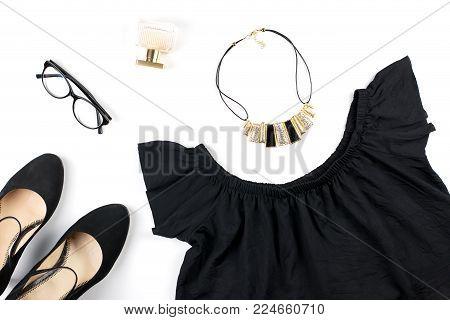 Woman clothes and accessories on white background. Total black look - black summer dress, heeled shoes, eyeglasses. Top view
