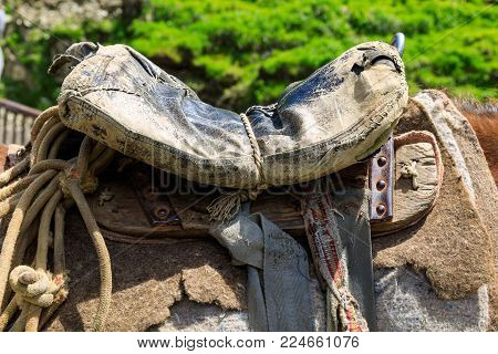 Threadbare old saddle on a shepherd's horse, handmade saddle of a peasant shepherd.