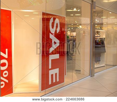 Sale banner signs in shop window at fashion store in shopping mall