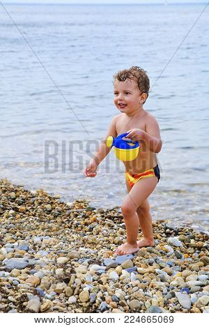 Happy little child, adorable brown-haired toddler playing on the beach with toys