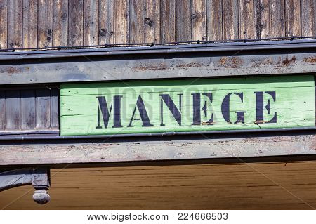 vintage sign at the entrance of an equestrian carousel on which is inscribed the word carousel (