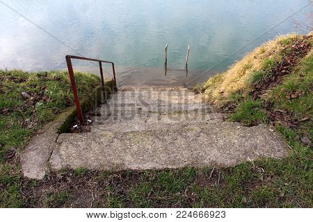Concrete steps with metal handrail on river bank with uncut grass leading to flooded lower level and another metal handrail