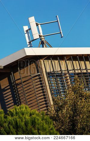 view of low energy modern building with a mini wind turbine on the roof
