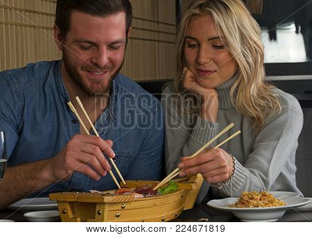 Caucasian young couple eat from sushi wood boat at restaurant.