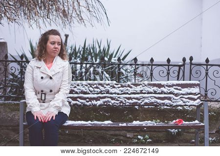 Sad woman sitting alone in a bench next to a pink rose in winter. Valentine's Day concept.