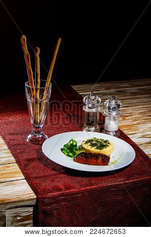 Still life fresh Omelet with Salmon under the black sesame seeds near Salad, Bread Sticks, Salt and Pepper on the wooden table with red tablecloth. Dark theme, with copyspace.