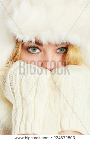 Winter clothing, fashion concept. Closeup of young blue eyed woman covering her face with hands wearing white gloves. Attractive lady in wintertime clothes fur cap, studio shot