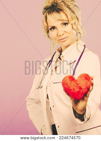 Help people concept. Medical idea of helping. Mature blonde happy doctor cardiologist with red heart enjoy her work. Middle aged woman wearing medic apron. Filtered.