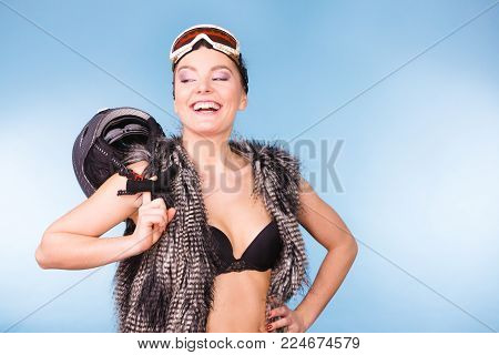 Winter sport activity concept. Atractive smiling woman wearing black bra, ski goggles and furry waistcoat holding helmet, blue background studio shot.