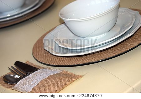 table setting silverware and white dinnerware place setting with burlap