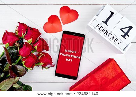 Bouquet of red roses, two hearts, mobile hone with sign Happy Valentines Day, gift box and february 14 wooden calendar, copy space. Greeting card mockup. Top view, flat lay. Love concept