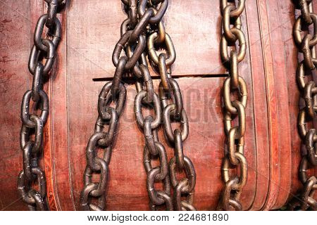 A large, brown, wooden casket, a piggy bank, a chest bound, closed with iron strong chains.