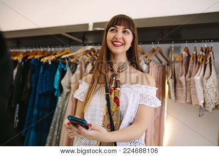 Fashion designer trying new designer clothes on a model. Woman entrepreneur in her cloth shop designing new clothes.