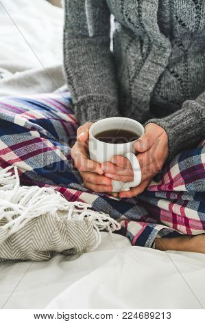 Woman wearing cozy pyjamas and gray cardigan drinking tea on a bed