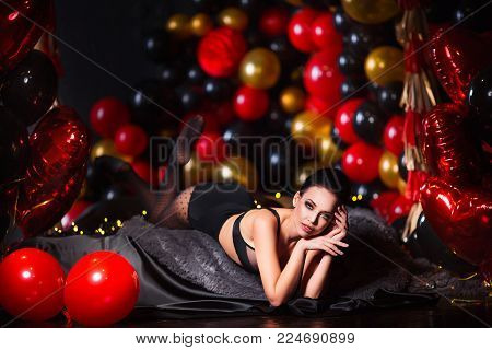 Perfect, sexy body and breast of young woman wearing seductive lingerie and black tights. Beautiful hot female in underwear posing in sensual way in festive interior with balloons