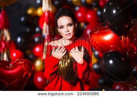 Young woman wearing red sweater and black tights holding heart. Beautiful hot female posing in sensual way in St. Valentines day interior with balloons