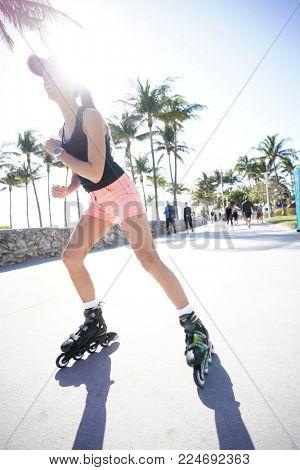 Trendy girl roller-skating in Miami South Beach promenade