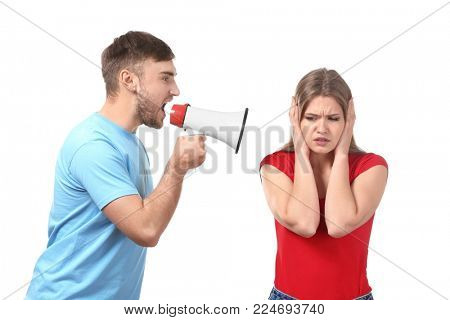Young man shouting into megaphone at woman on white background. Problems in relationship