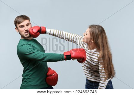 Couple fighting in boxing gloves on light background. Problems in relationship