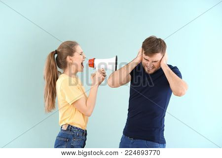 Young woman shouting into megaphone at man on color background. Problems in relationship
