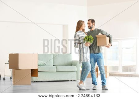 Young man holding moving box and woman with houseplant in room at new home
