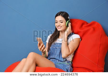 Woman listening to audiobook through headphones on color background