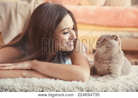 Young woman with cute pet cat on floor at home