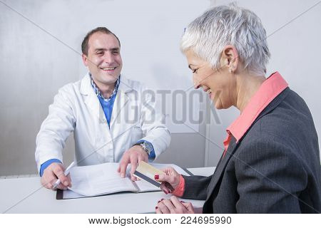Senior woman paying her medical bill at the clinic with her credit card
