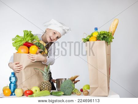 Girl In Chef Hat Holding A Tape Measure At The Package Of Food. A Variety Of Fresh Vegetables And Fr