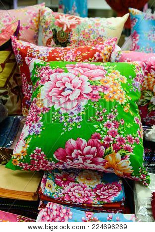 Pile of pillow with many coloured flowers