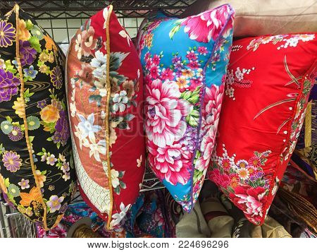 Pile of pillow with many coloured flowers in shop