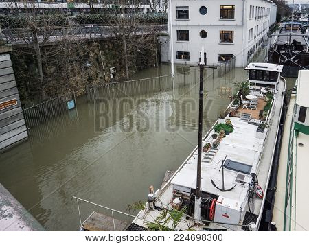 PARIS, FRANCE - JAN 30, 2018: Port Autonome de Paris building covered with water and nearby peniche barge after Swollen river Seine river's embankments overflow after days of heavy rain
