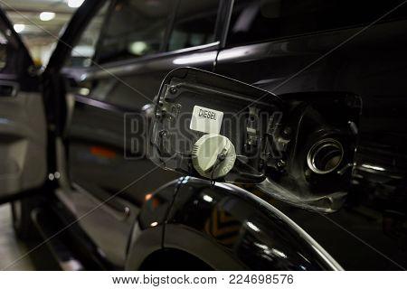 Opened fuel cap of black car at underground parking.