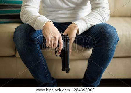 Close up of young man sitting on sofa with a gun in hand