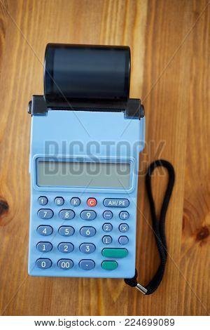 Mobile cash register on wooden desk.