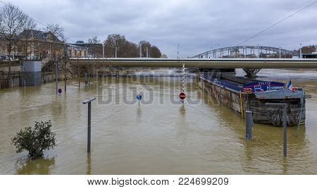 PARIS,FRANCE - January 29, 2018: The Seine River rises significantly, increasing the risk of flooding in Paris during the last days of January 2018. Here is the Austerlitz area of the river, featuring the Charles-de-Gaulle bridge.