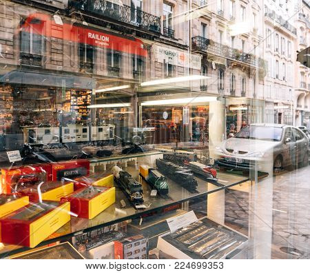 PARIS, FRANCE - JAN 30, 2018: Reflection Store window facade selling multiple toy collectible model trains featuring all railways in the world in central Paris, France